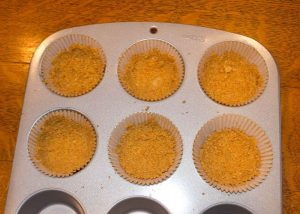 Marijuana Cheesecake Crusts in a muffin tin, now ready for filling batter.